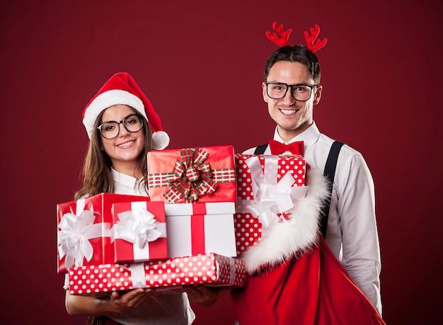 Porträt des lächelnden paares mit stapel von weihnachtsgeschenken