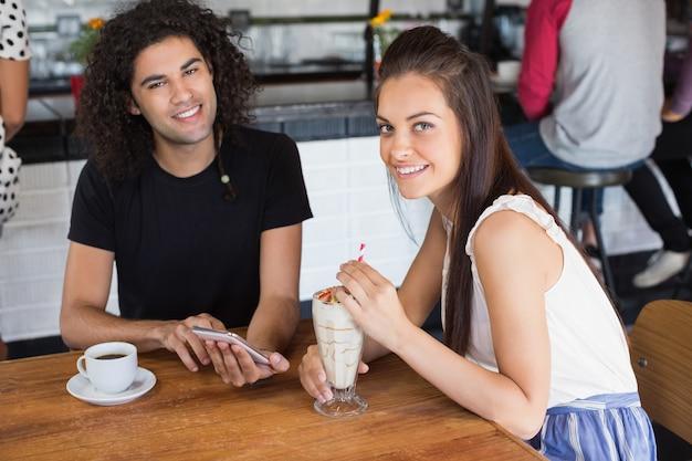 Porträt des lächelnden paares unter verwendung des mobiltelefons beim trinken im restaurant