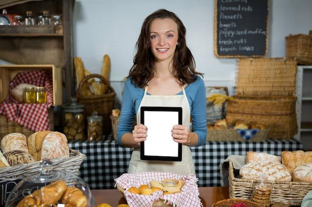 Porträt des lächelnden personals, das digitales tablett am backschalter zeigt