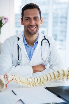 Porträt des lächelnden physiotherapeuten, der mit wirbelsäulenmodell sitzt