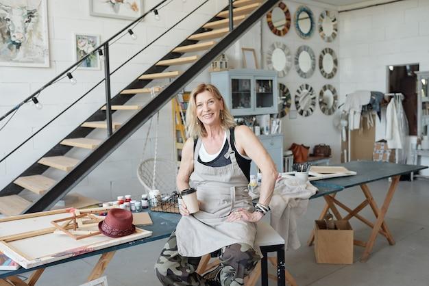 Porträt des lächelnden reifen künstlers, der im kunststudio mit bildern sitzt und kaffee trinkt