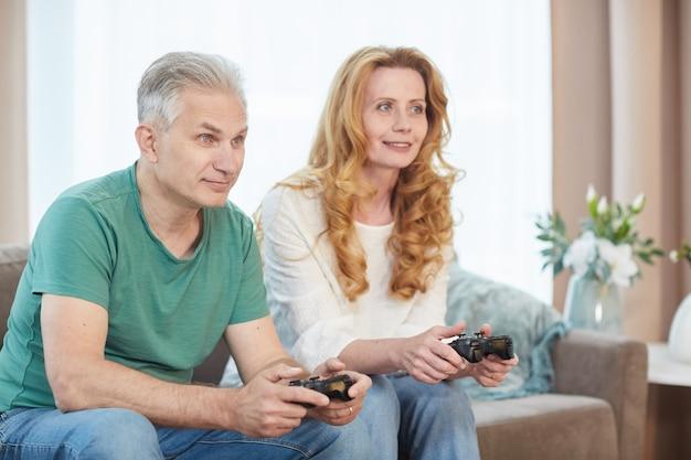 Porträt des lächelnden reifen paares, das videospiele über konsole spielt und controller hält, während zeit zu hause genießt