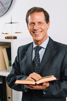 Porträt des lächelnden reifen rechtsanwalts, der gesetzbuch hält
