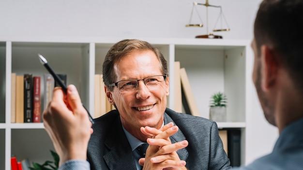Porträt des lächelnden reifen rechtsanwalts, der mit geschäftskundenbehälter sitzt