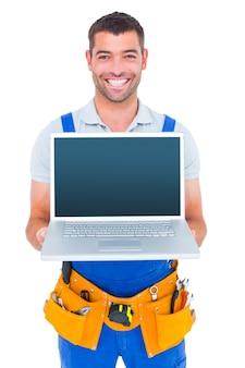 Porträt des lächelnden schlossers laptop zeigend