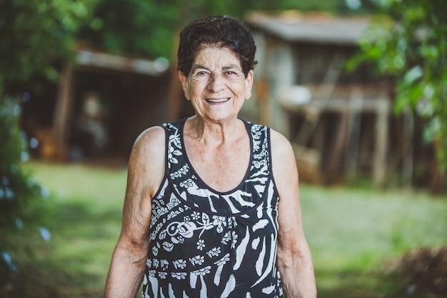Porträt des lächelnden schönen älteren weiblichen landwirts