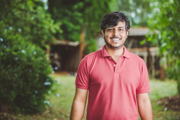 Porträt des lächelnden schönen jungen männlichen landwirts