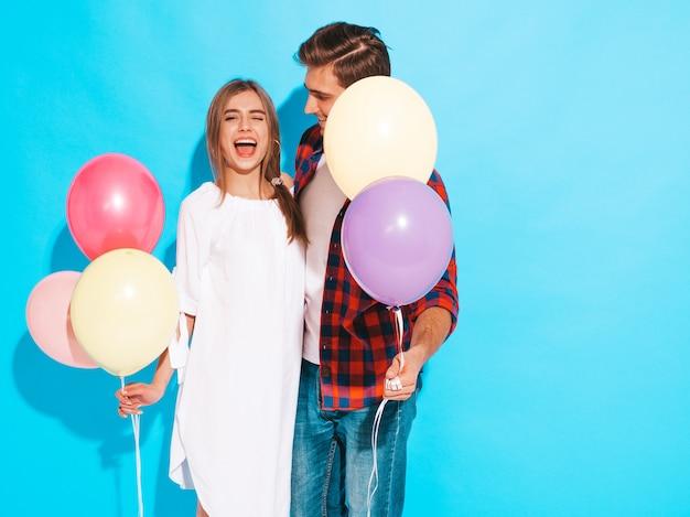 Porträt des lächelnden schönen mädchens und ihres hübschen freundes, die bündel bunte ballone und lachen hält. alles gute zum geburtstag