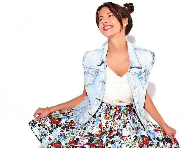 Porträt des lächelnden schönen niedlichen brünetten frauenmodells in lässiger sommerjeanskleidung ohne make-up mit hörnerfrisur lokalisiert auf weiß. kleid in händen
