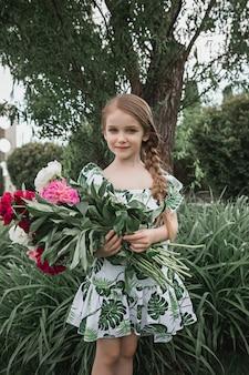 Porträt des lächelnden schönen teenager-mädchens mit blumenstrauß der pfingstrosen gegen grünes gras am sommerpark. kindermode-konzept.