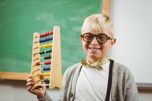 Porträt des lächelnden schülers kleidete oben als der lehrer an, der abakus in einem klassenzimmer hält