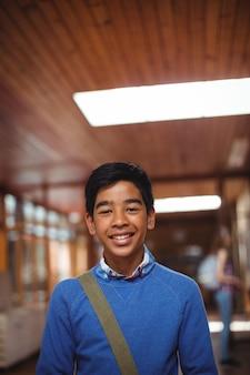 Porträt des lächelnden schuljungen, der im korridor steht