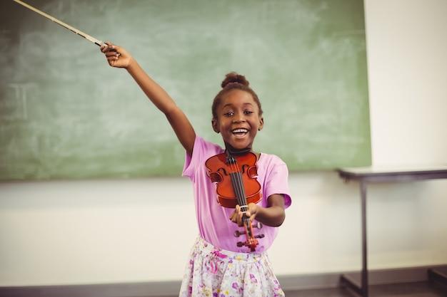 Porträt des lächelnden schulmädchens violine im klassenzimmer spielend