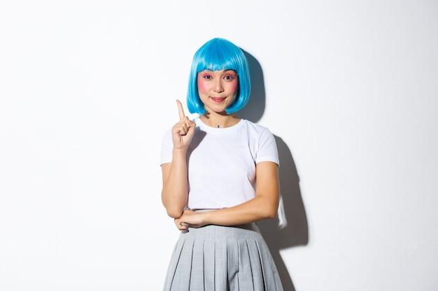 Porträt des lächelnden selbstbewussten asiatischen mädchens in der blauen perücke und im halloween-kostüm, das lösung hat, finger in eureka-geste hebend, stehend.