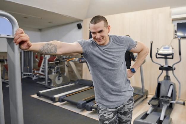 Porträt des lächelnden starken muskulösen mannes der junge in der turnhalle