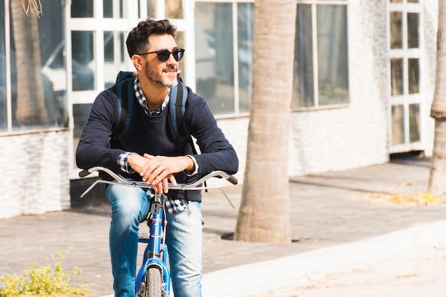 Porträt des lächelnden stilvollen mannes mit seinem rucksack, der auf seinem fahrrad weg schaut sitzt
