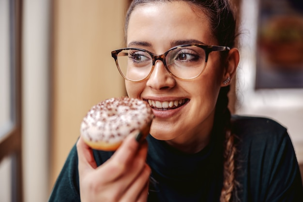 Porträt des lächelnden teenager-mädchens, das an der konditorei sitzt, donut hält und freizeit genießt.