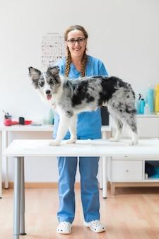 Porträt des lächelnden tierarztes mit hund auf tabelle in der klinik