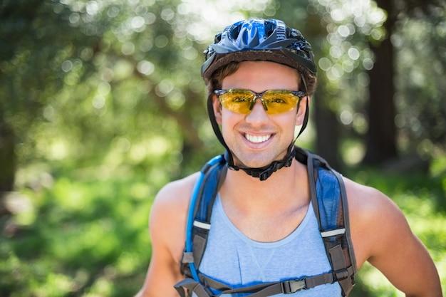 Porträt des lächelnden tragenden sturzhelms des mannes