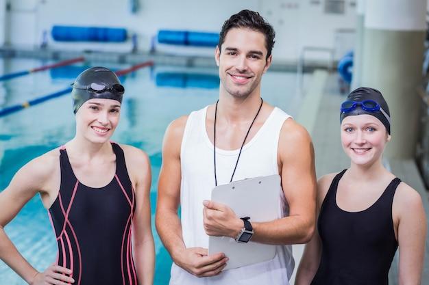 Porträt des lächelnden trainers und der schwimmer im freizeitzentrum