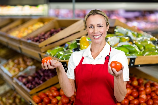 Porträt des lächelnden verkäufers tomaten halten