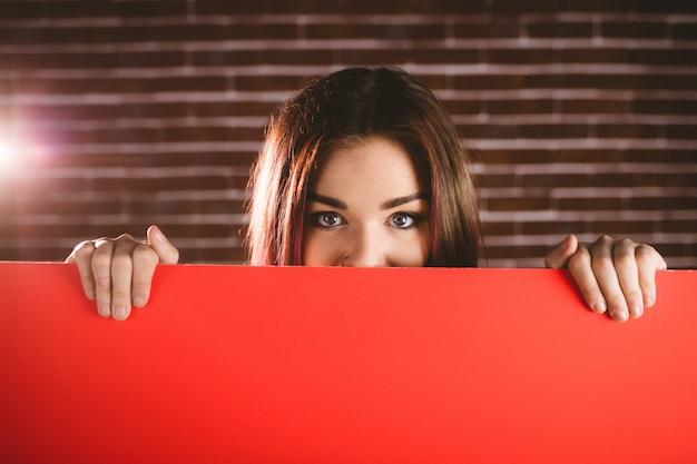 Porträt des lächelnden versteckenden gesichtes der frau vom leeren plakat