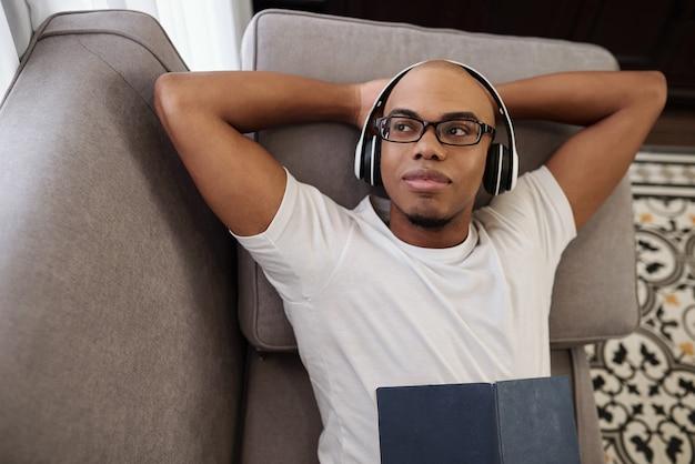 Porträt des lächelnden verträumten jungen schwarzen mannes, der auf sofa in den kopfhörern ruht und wegschaut