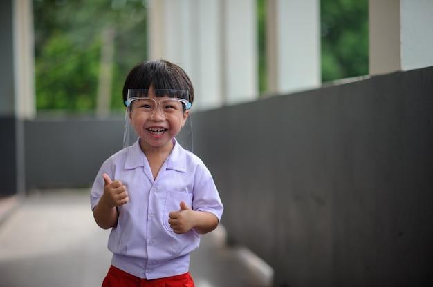 Porträt des lächelnden vorschulkindes, das gesichtsschutz neuen normalen lebensstil an öffentlichen orten trägt.