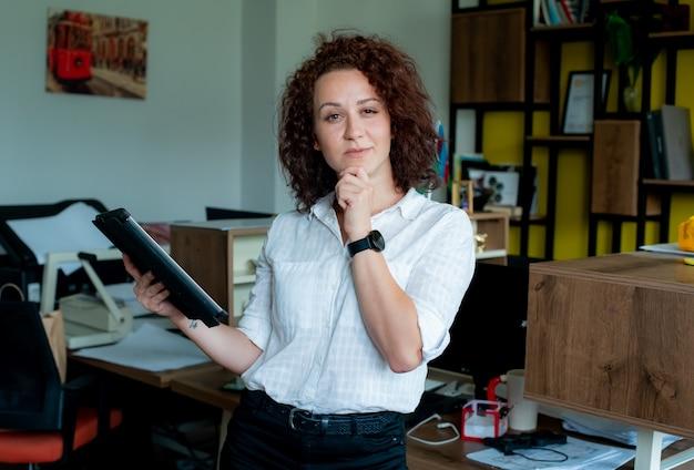 Porträt des lächelnden weiblichen angestellten, der tablette hält, kamera mit nachdenklichem ausdruck mit hand auf kinn denkend betrachtet, das sicheres tragen des weißen hemdes stehend im büro denkt