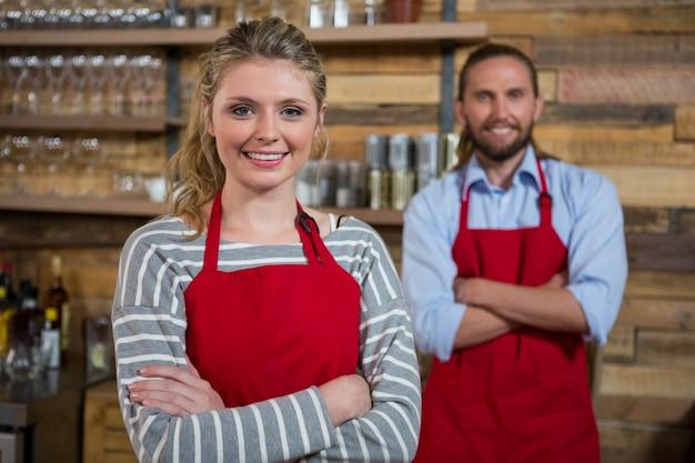 Porträt des lächelnden weiblichen barista mit männlichem mitarbeiter im coffeeshop