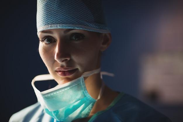 Porträt des lächelnden weiblichen chirurgen im operationssaal