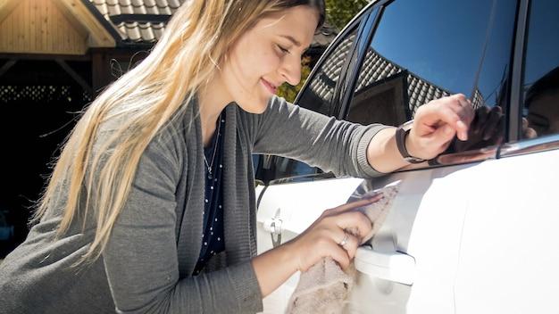 Porträt des lächelnden weiblichen fahrers, der ihr auto mit tuch poliert.