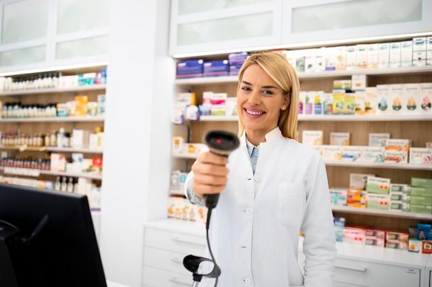 Porträt des lächelnden weiblichen kaukasischen apothekers, der in der drogerie steht und strichcodeleser hält.