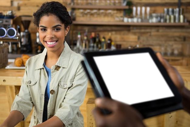 Porträt des lächelnden weiblichen kunden mit barista, der tablet pc im vordergrund am café hält