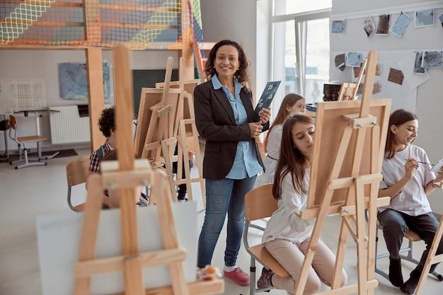 Porträt des lächelnden weiblichen lehrers im modernen klassenzimmer mit kinder, die lektion im hintergrund zeichnen