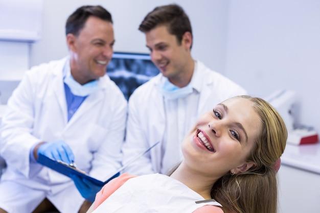 Porträt des lächelnden weiblichen patienten, der auf zahnarztstuhl sitzt