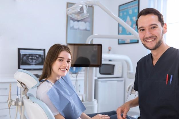 Porträt des lächelnden weiblichen patienten und des zahnarztes in der klinik