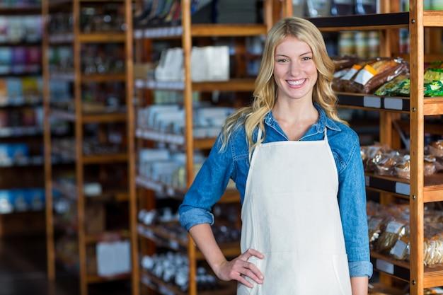 Porträt des lächelnden weiblichen personals, das mit hand auf hüfte steht