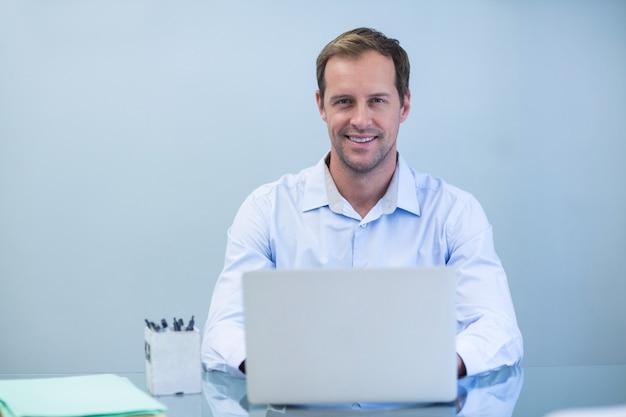 Porträt des lächelnden zahnarztes, der am laptop arbeitet