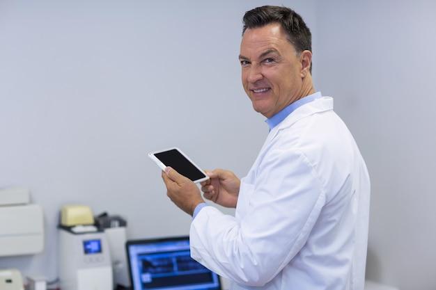 Porträt des lächelnden zahnarztes, der digitale tablette hält