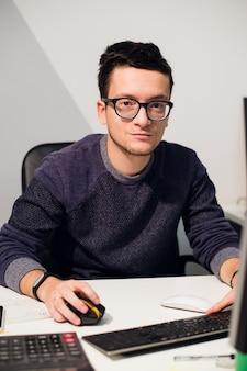 Porträt des lächelnden zufälligen geschäftsmannes, der mit computer im büro arbeitet