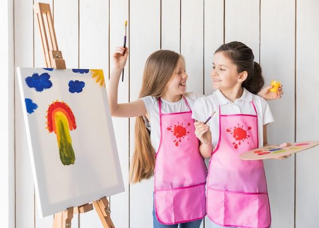 Porträt des lächelns von zwei mädchen im rosa schutzblech, das spaß beim malen auf dem segeltuch macht