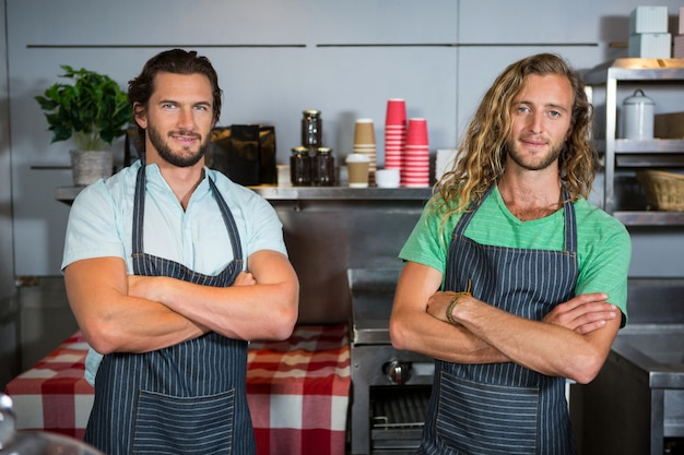 Porträt des lächelns zweier männlicher mitarbeiter, die mit verschränkten armen stehen
