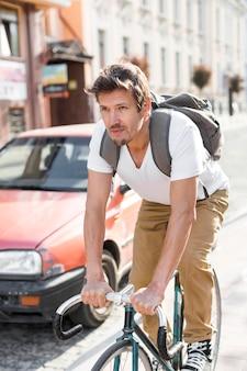 Porträt des lässigen männlichen fahrrads in der stadt