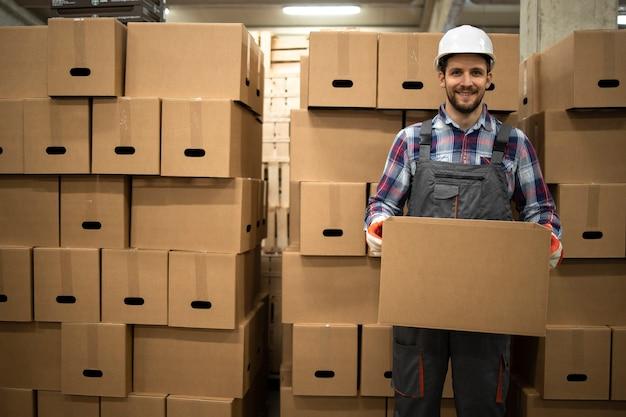 Porträt des lagerarbeiters in der arbeitskleidung und im helm, der pappkarton hält, der waren im fabriklager verlagert.