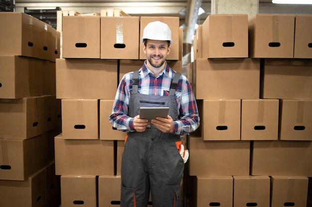 Porträt des lagerverwalters, der tablet-computer hält und durch pappkartons mit waren im fabriklagerraum steht.