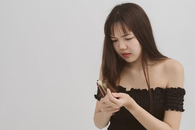 Porträt des langen haares der asiatischen frau mit einem kamm und einem problemhaar auf weiß. dieses bild gegen haarausfall. copyspace.