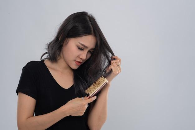 Porträt des langen haares der asiatischen frau mit einem kamm und problemhaar auf weißem hintergrund.