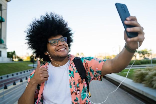 Porträt des lateinischen mannes, der ein selfie mit seinem handy nimmt, während draußen auf der straße stehend.
