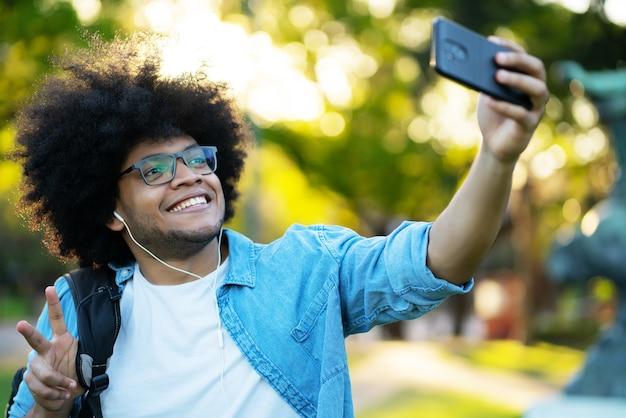 Porträt des lateinischen mannes, der ein selfie mit seinem handy nimmt, während draußen auf der straße stehend